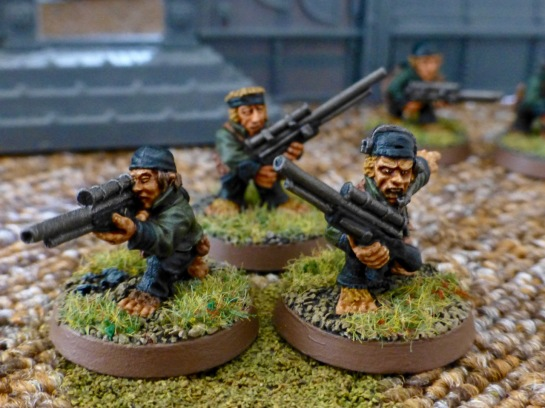 Group of three Halfling models wearing green uniform jackets and holding rifles