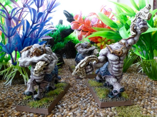 Three purplish centaur creatures with organic looking guns moving between brightly coloured jungle plants
