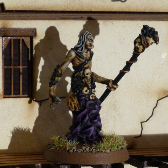Necromancer with clawlike hands holding a staff with a decapitated head