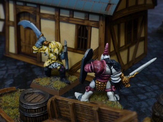 Chaos Warriors facing each other with raised swords outside a hovel
