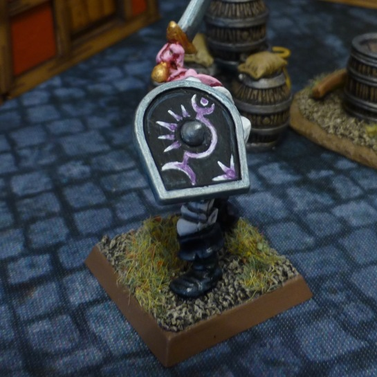 Chaos Warrior holding shield aloft displaying purple ornaments on a black background