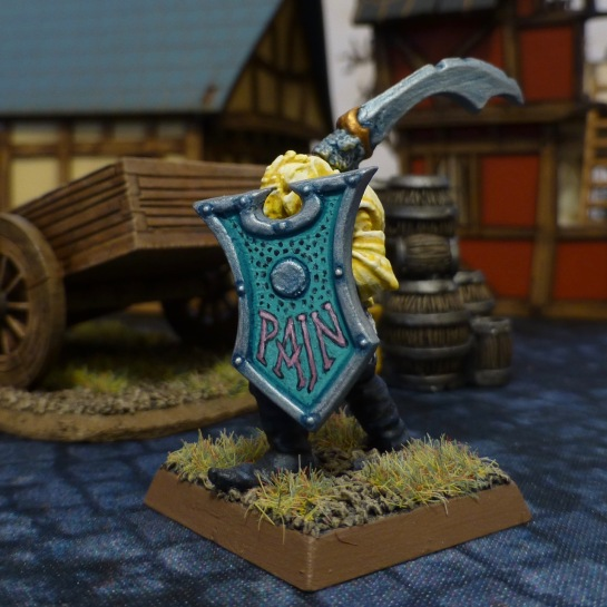 Chaos Warrior in yellow armour holding a turquoise shield with the word Pain painted on