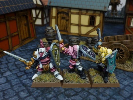 Three old school Chaos Warriors in pastel armour on a town square in front of a wooden cart