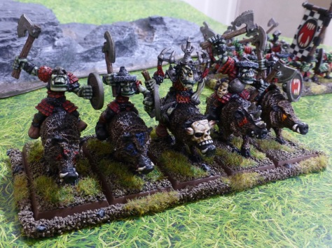 Five orcs in red scale armour riding on wild boars