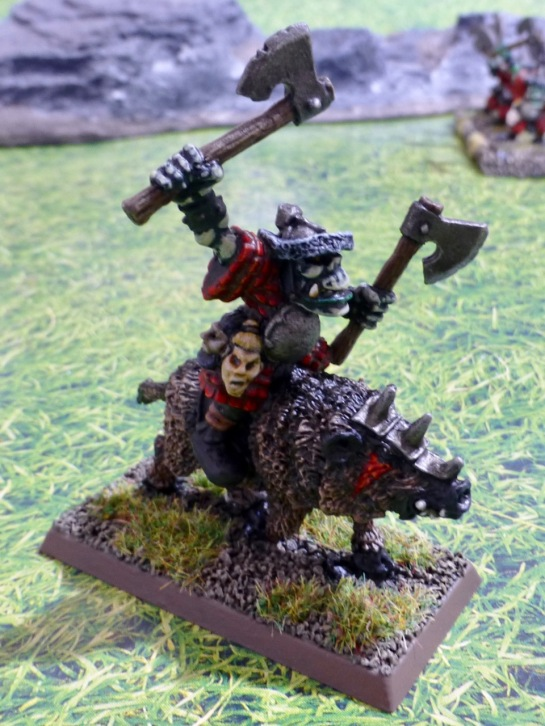 An orc wielding two axes riding a war boar
