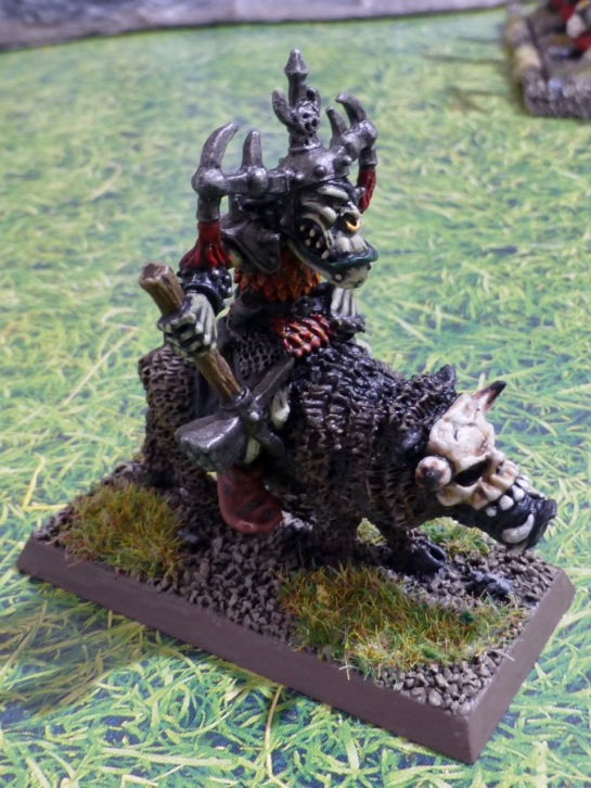 An orc with a warhammer sitting astride a boar with a skull mask