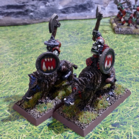 Two orcs riding boars with axes and shields
