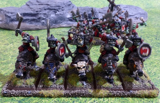 Five or boar riders and a regiment of orcs on foot in the background