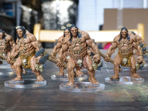 Painted figures of loin cloth clad barbarians carrying stone axes and shrunken heads