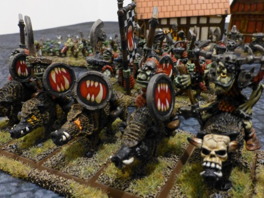 Orcs on boars bearing shields with gaping maws full of teeth painted on