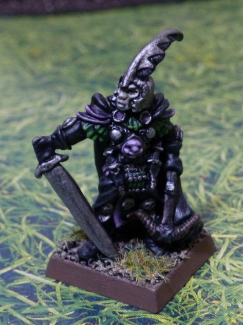 Miniature figure of a Dark Elf with black, purple, green and silver armour and clothing