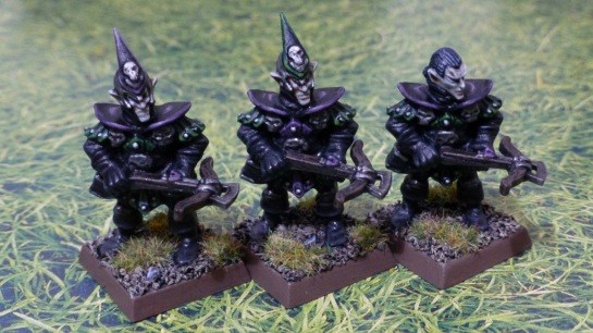 Three Dark Elf miniatures carrying crossbows