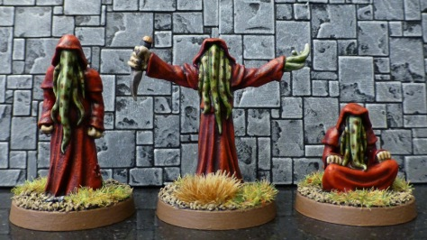 Three humanoid figures in red robes with tentacles in place of faces