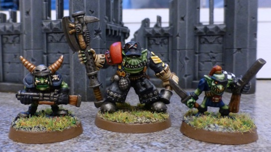Space Ork with heavy grey coat and power axe, flanked by two Gretchin with shotguns