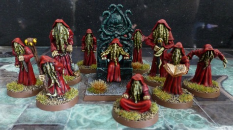 Group of ten humanoid creatures in red robes and with green tentacles for faces
