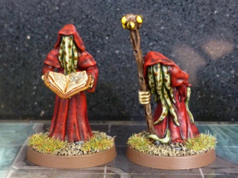 Two robed figures with a staff and grimoire
