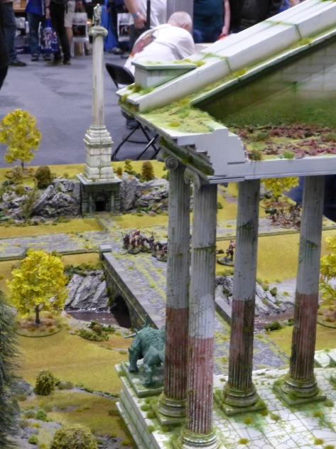 View from behind classical pillars onto a green landscape and stone bridge