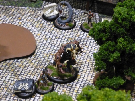 Large beastman, giant snake and human figures on a cobblestone square