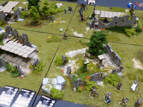 Ruins on green fields with skirmishing medieval style figures
