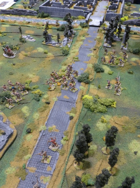 Paved road across green fields with marauding bands of barbarians and gnolls