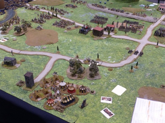 Encampment in green fields with regiments marching in the distance