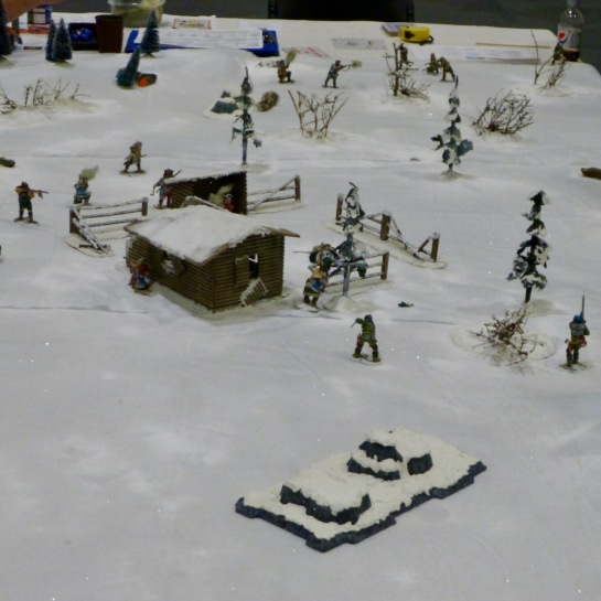 Log cabin in a snowy winter landscape with individual fighters skirmishing