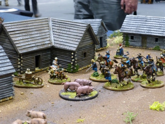 Troops moving through a hamlet with civilians and pigs