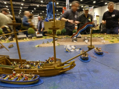 View from behind a sailing ship and row boats towards shore