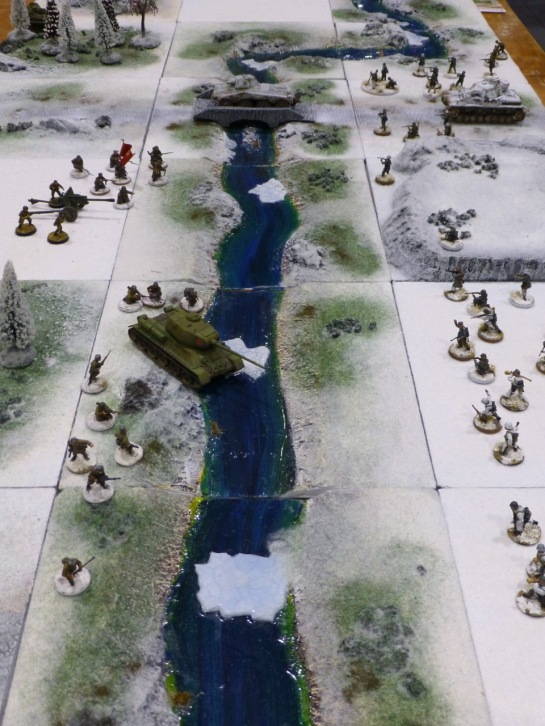 Infantry and tanks facing each other across a river in a snowy landscape