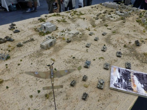 Desert wargaming table with tanks advancing and a plane above