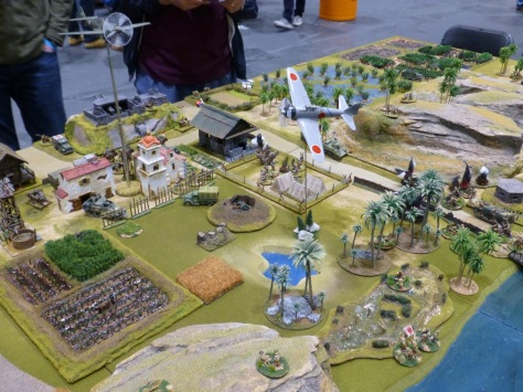 Wargames table with tropical terrain and fighter jets circling above