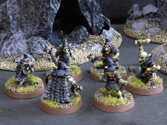 Circle of six goblins with black hoods in rocky terrain