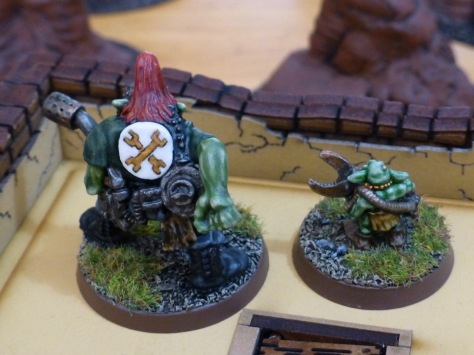 Back view of Space Ork displaying a backplate with crossed golden spanners and Gretchin from the roof of an adobe building