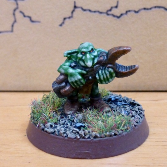 Diminutive green goblinoid creature holding a large rusty spanner