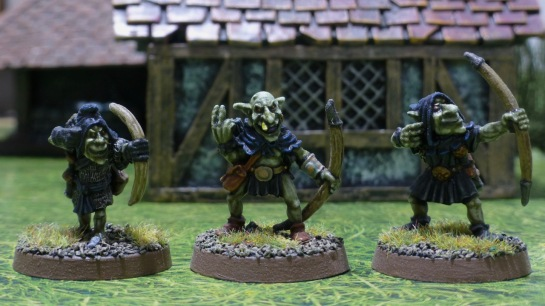 Three goblins with dark hoods carrying bows