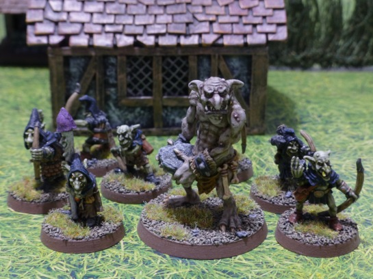 Groups of goblin archers, shaman and a large troll in front of a medieval hovel