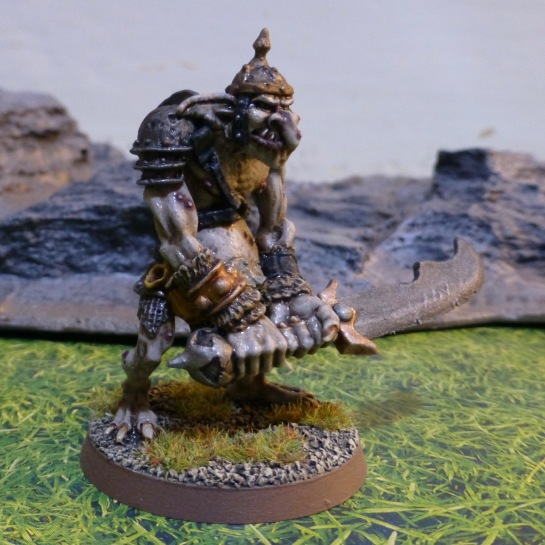 Side view of grey skinned troll with helmet and shoulder guard, gripping a double handed curved sword