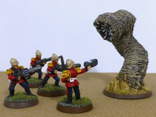 Four soldiers in red jackets aiming guns at a large worm that burst from the desert floor