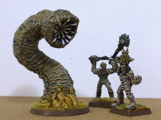 Two living mummies with weapons aloft next to a giant worm emerging from the sand