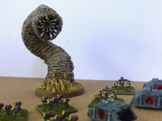 Giant sand worm with big maw towering over small infantry figures and tanks