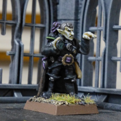Dark Elf Sorcerer in black clothes with silver skull cap, holding an amulet and pointing forward