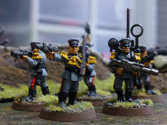 Soldiers in grey uniforms with laser rifles including a radio operator