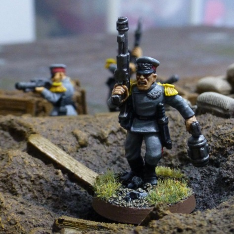 Soldier running through crater with laser rifle in right and bomb with handle in left hand