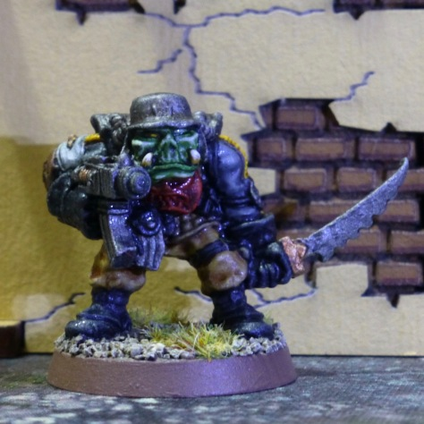 Space Ork with boltgun and sword in front of an adobe building