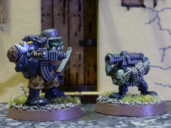 Space Ork with steel helmet and boltgun next to a Gretchin carrying a large boltgun on his back