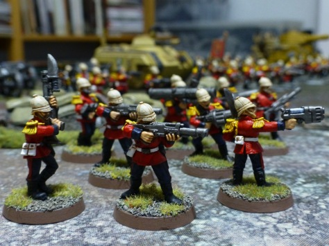 Soldiers with pith helmets and red uniform jackets aiming their weapons