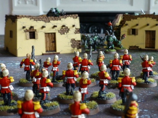 Ranks of soldiers in red jackets and tropical helmets advancing on two adobe buildings with Orks in the background