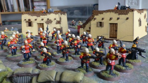 Several dozen troops marching in front of adobe buildings with heavy weapons on roofs
