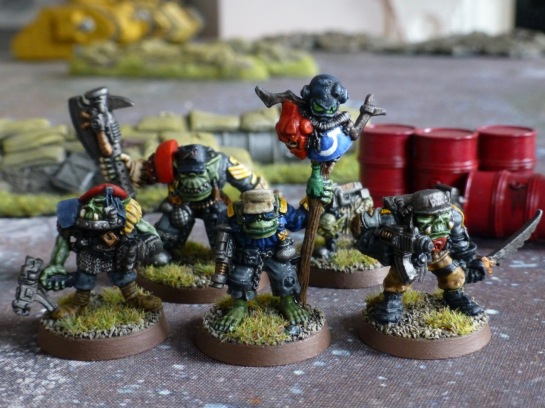 Green skinned Orks in ragged military gear and carrying a standard of Space Marine helmets