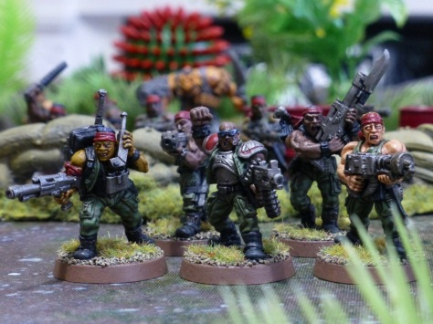 Squad of five soldiers in green uniforms and red bandanas amongst jungle plants